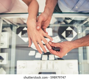 Cropped image of beautiful couple choosing wedding ring in the shopping mall