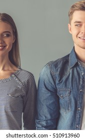 Cropped image of beautiful couple looking at each other and smiling while standing straight on gray background