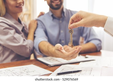 Cropped image of beautiful couple taking keys from the realtor and smiling
