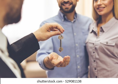 Cropped image of beautiful couple taking keys from realtor and smiling