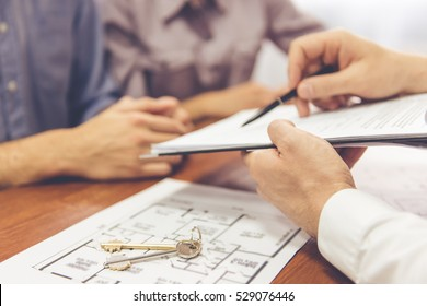 Cropped image of beautiful couple talking with realtor, who is showing where to sign the documents