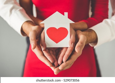 Cropped image of beautiful elegant couple holding a paper house with heart, on gray background