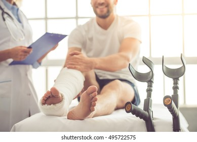 Cropped image of beautiful female medical doctor listening to handsome patient with broken leg and making notes while working in her office