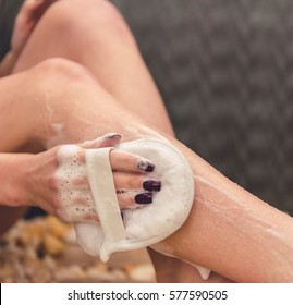 Cropped image of beautiful girl cleaning her legs using a loofah while taking shower in bathroom