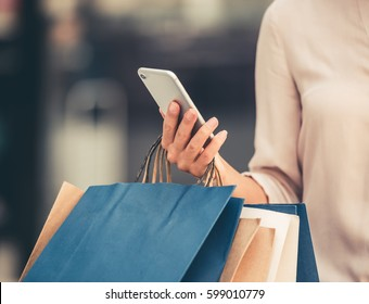Cropped image of beautiful girl holding shopping bags and using a smart phone while doing shopping in the mall