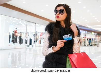 Cropped image of beautiful girl with shopping bags and credit card doing shopping in the mall. Pretentious fashion model in sunglasses on the background of superstore