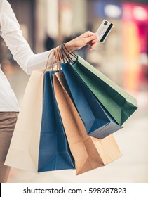 Cropped image of beautiful girl with shopping bags and credit card doing shopping in the mall