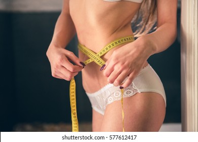 Cropped image of beautiful girl in white lingerie measuring her waist using a tape measure while standing in bathroom
