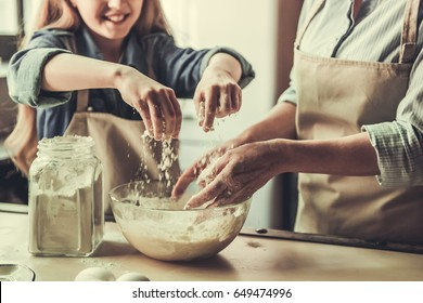 Cropped image of beautiful grandma and granddaughter kneading dough and smiling while baking in kitchen
