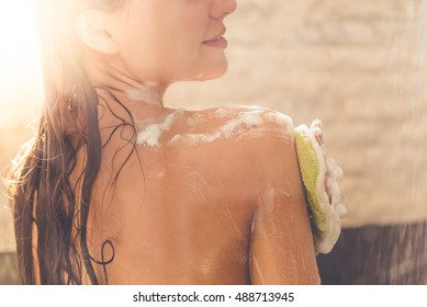 Cropped image of beautiful naked young woman smiling while taking shower in bathroom