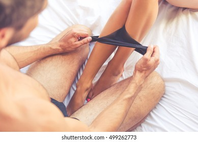 Cropped image of beautiful passionate couple having sex on bed. Man is putting off his partner's black panties