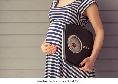Cropped image of beautiful pregnant woman holding weigh scales and keeping one hand on a belly, standing against gray wall