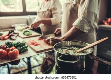 Cropped image of beautiful senior couple in aprons cooking together in kitchen