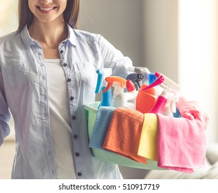 Cropped image of beautiful woman smiling while holding a basin with detergents and rags ready to clean her house