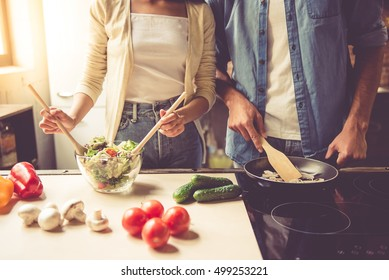 Cropped image of beautiful young couple cooking in kitchen at home