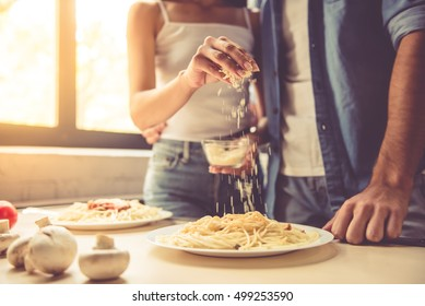 Cropped image of beautiful young couple eating spaghetti in kitchen at home. Woman is adding grated cheese