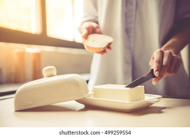 Cropped image of beautiful young girl making a toast with butter in kitchen at home