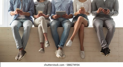 Cropped image of beautiful young people in casual clothes using gadgets while sitting together on the window sill
