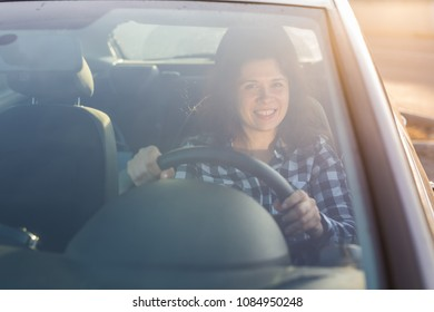 Cropped image of beautiful young woman driving a car and smiling