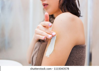 Cropped image of beautiful young woman in bath towel applying body lotion on her shoulders and standing in bathroom. Spa, care concepts