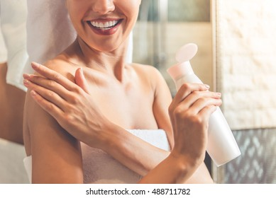 Cropped image of beautiful young woman in bath towel applying body lotion on her shoulders and smiling while standing in bathroom
