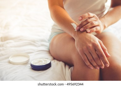 Cropped image of beautiful young woman applying hand cream while sitting on bed at home
