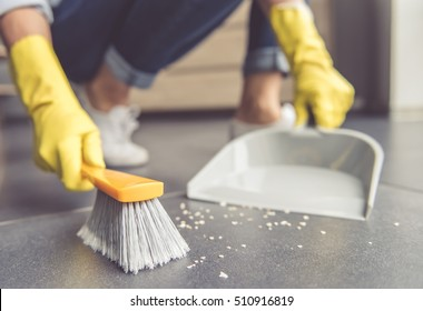 Cropped image of beautiful young woman using a dust pan and a brush while cleaning the floor at home