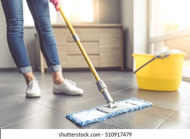Cropped image of beautiful young woman in protective gloves using a flat wet-mop while cleaning floor in the house