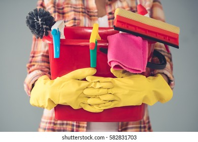 Cropped image of beautiful young woman in protective gloves holding a bucket with things for cleaning, on gray background