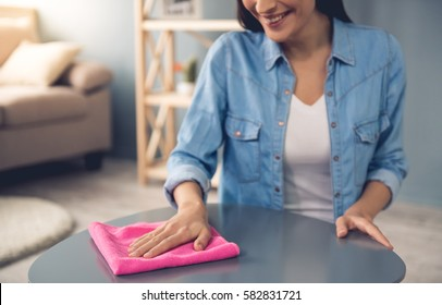 Cropped image of beautiful young woman using a rag and smiling while cleaning furniture at home