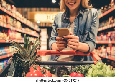 Cropped image of beautiful young woman using a smart phone and smiling while doing shopping at the supermarket