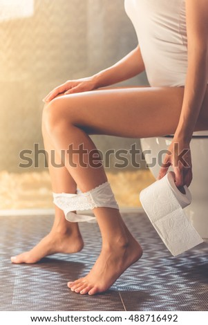 Cropped image of beautiful young woman holding a toilet paper while sitting on toilet