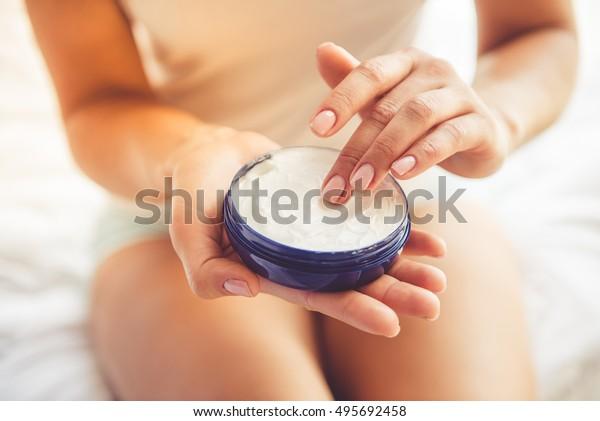 家で寝ながらクリームを塗る美しい若い女性のクロップ画像