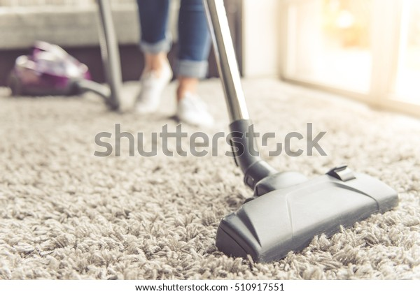 Cropped image of beautiful young woman using a vacuum cleaner while cleaning carpet in the house