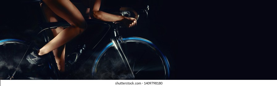 Cropped image bicycle wheels motion digital art effect body part slim legs of woman riding on bicycle aside, studio shot horizontal photo on black background with copy free pace for advertisement text