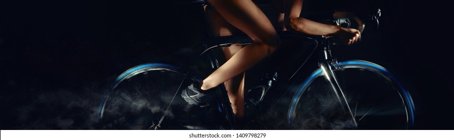 Cropped image bicycle wheels motion digital art effect body part slim legs of woman riding on bicycle, studio shot horizontal photo on black background with copy free pace for advertisement text