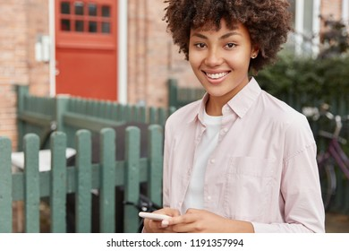 Cropped image of black woman with Afro haircut, uses mobile phone, satisfied with networking, poses outdoor in private sector near her house, checks notification, has toothy smile. Hipster blogger