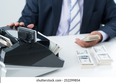 Cropped image of bookkeeper using money counting machine