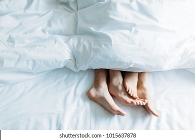 cropped image of boyfriend and girlfriend lying in bed under blanket