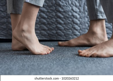 cropped image of boyfriend and girlfriend standing barefoot on floor