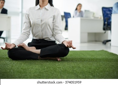 Cropped image of business lady practicing yoga in the office