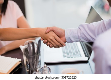 Cropped image of business partners shaking hands, selective focus