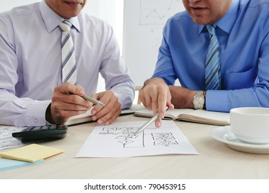 Cropped image of business people discussing chart