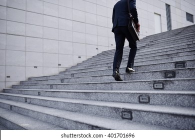 Cropped image of business person going up the stairs