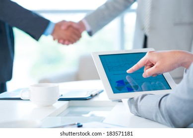 Cropped image of a business person pointing at the company activity diagram on the foreground, colleagues handshaking on the background