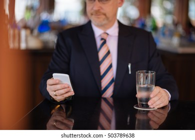 Cropped image of business person texting when having drink in cafe