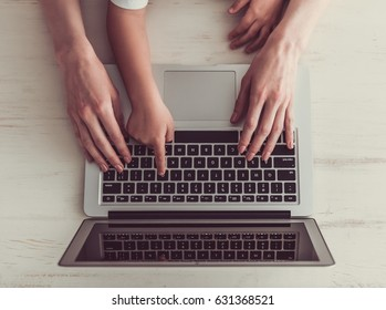 Cropped image of business woman and her little son using a laptop in office