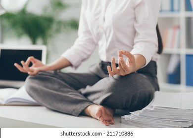 Cropped image of business woman practicing yoga in the office
