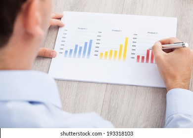 Cropped image of businessman analyzing graph at desk in office