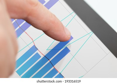 Cropped image of businessman analyzing graphs on digital tablet